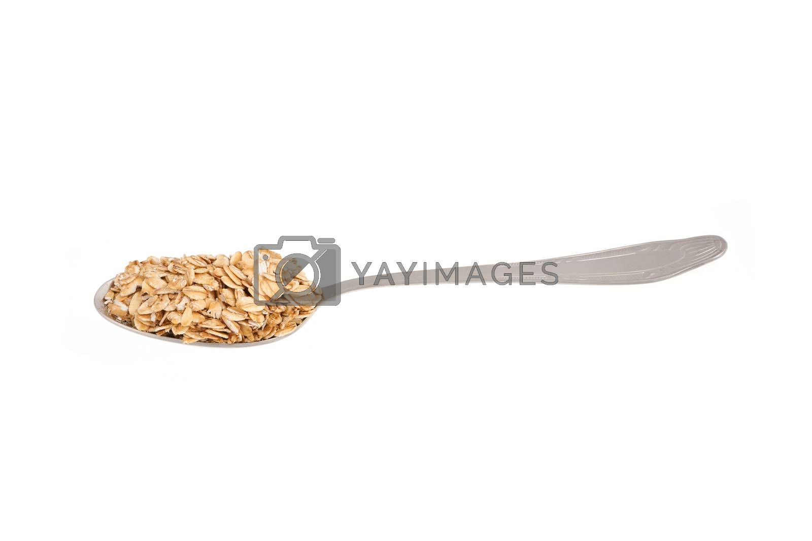 Oat flakes on metal spoon - isolated on a white background