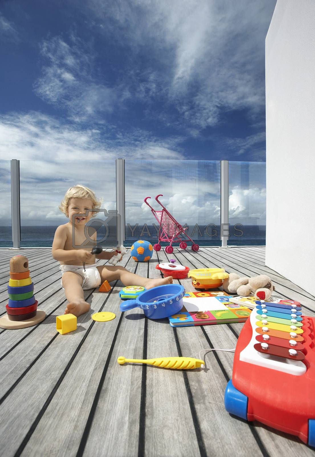 Royalty free image of Baby Boy Playing on Porch with lots of toys by moodboard