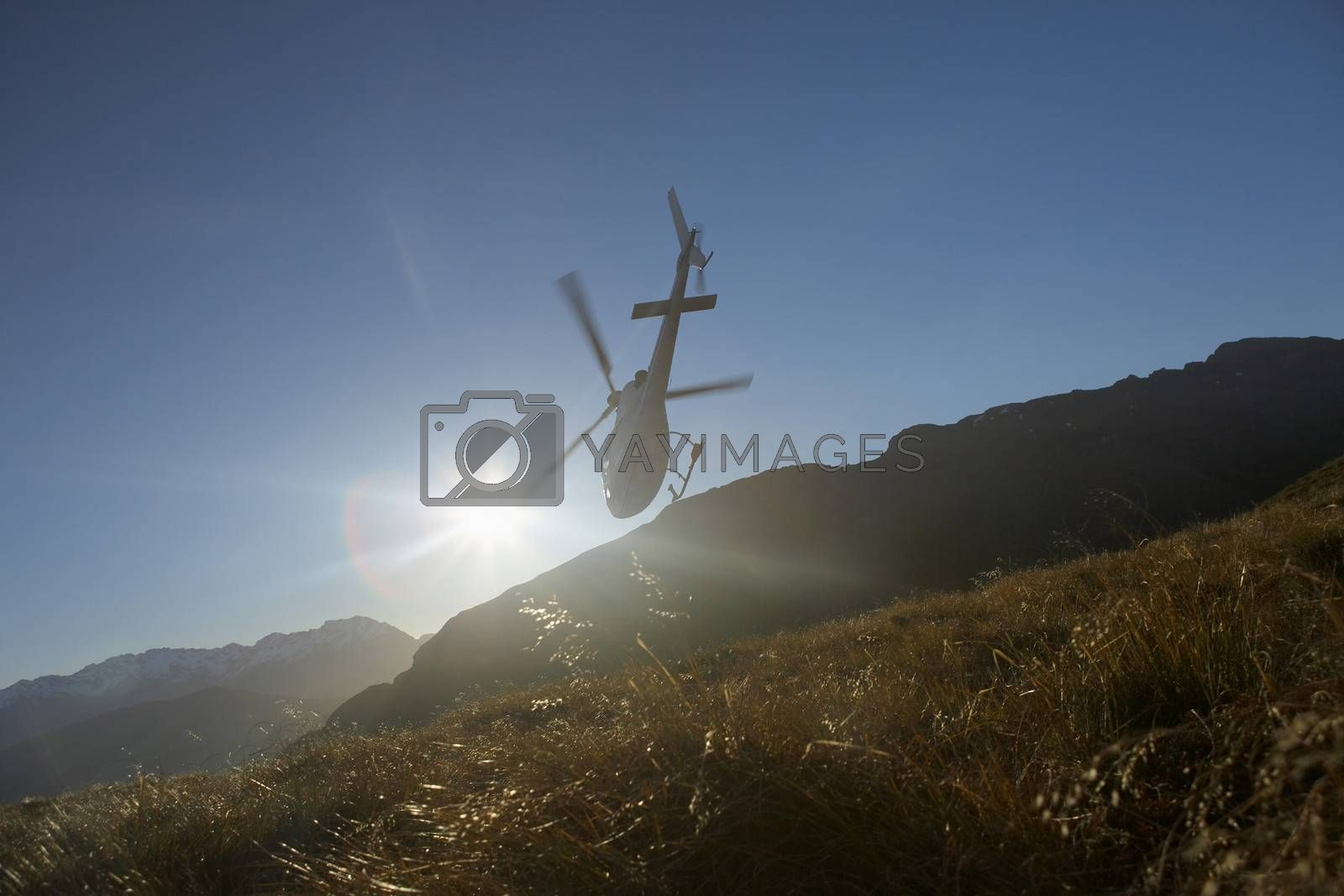 Helicopter Flying Over Hills In Front Of The Sun