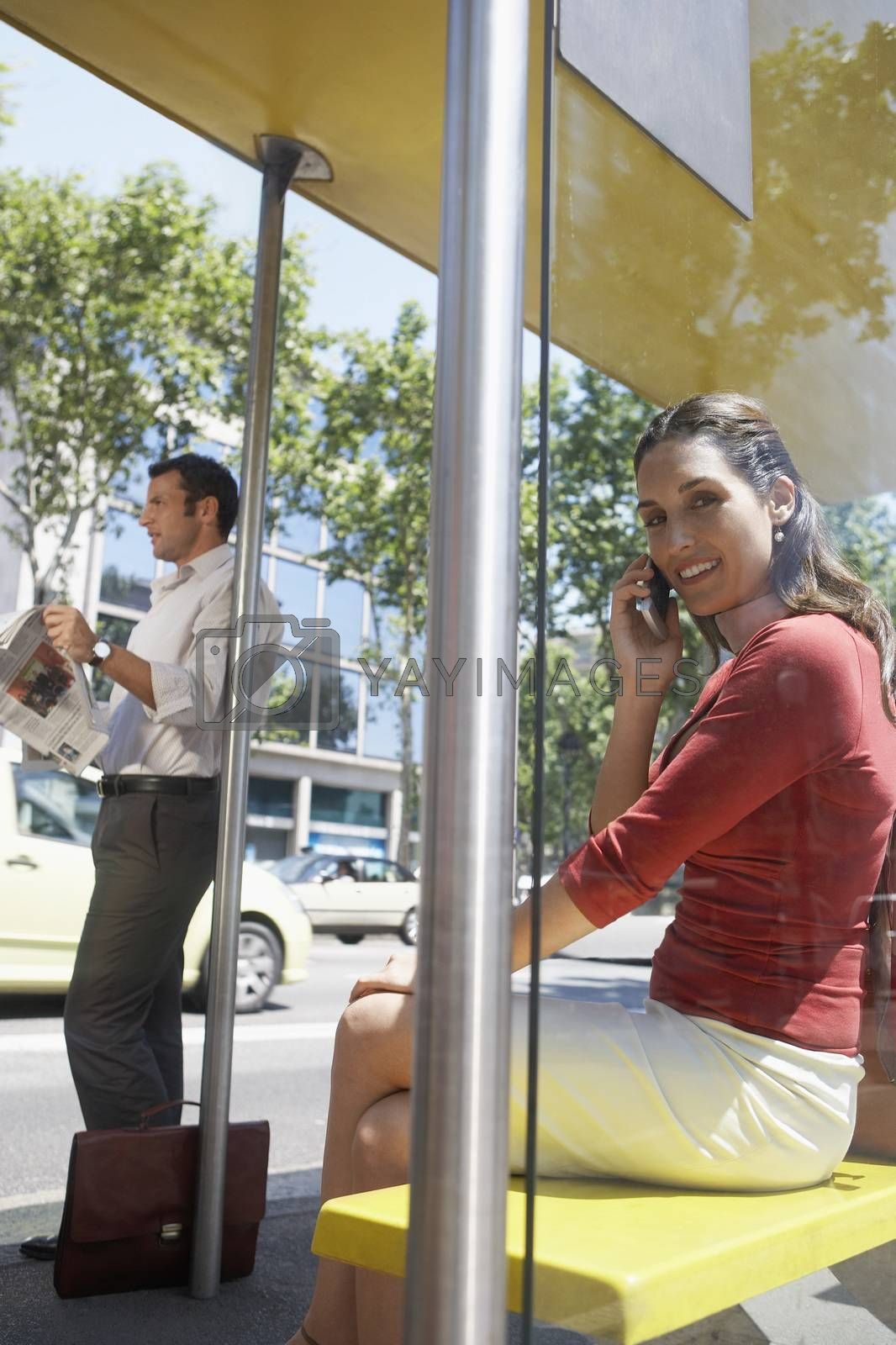Portrait of a woman on a call while man waiting for a bus at bus stop by moodboard