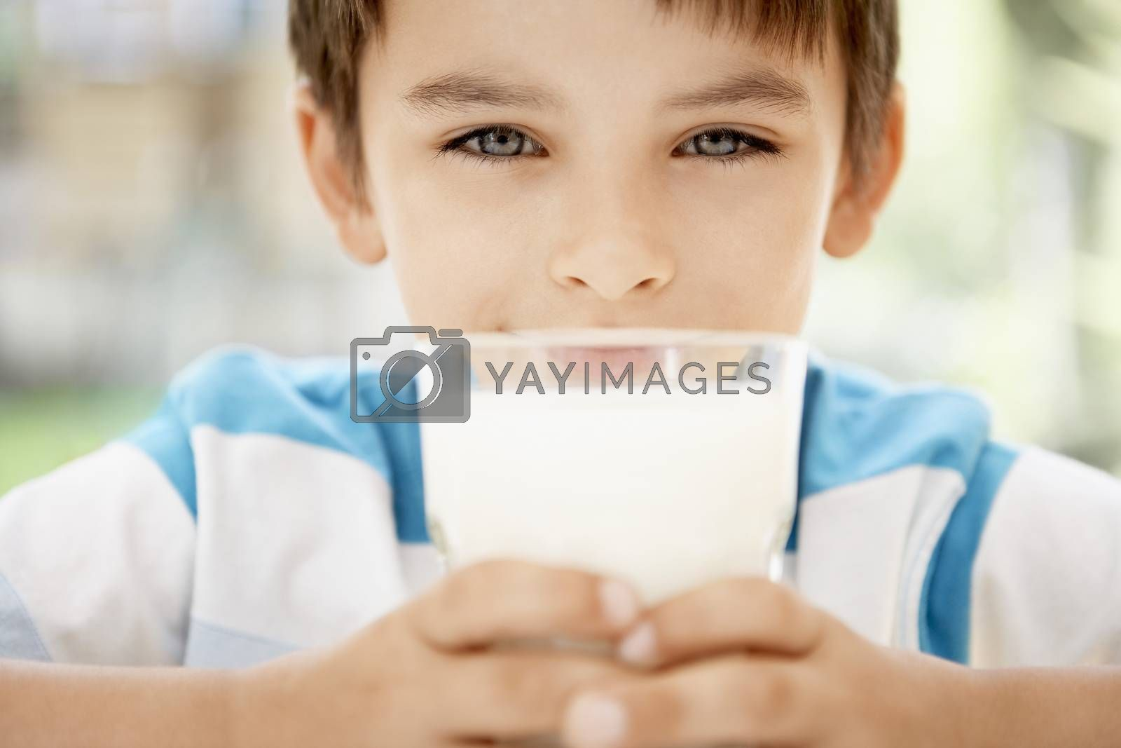 Royalty free image of Young boy holding glass of milk portrait close up by moodboard