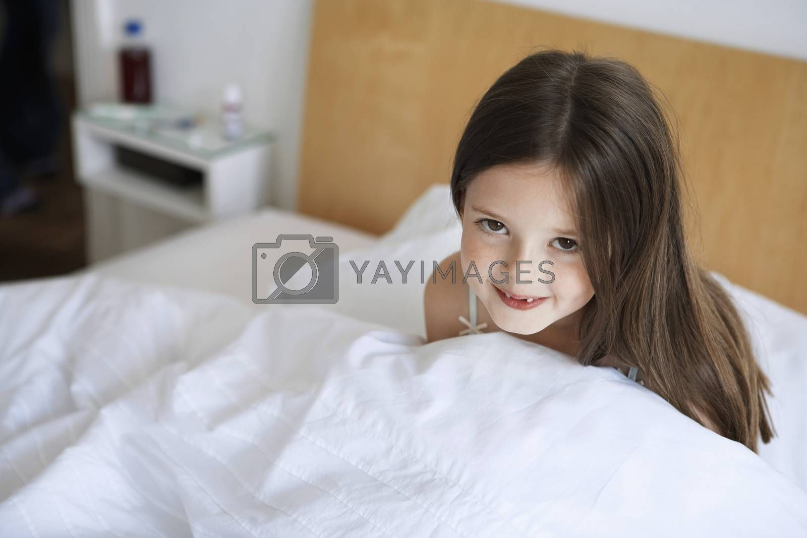 Royalty free image of Little girl sitting up in bed portrait by moodboard