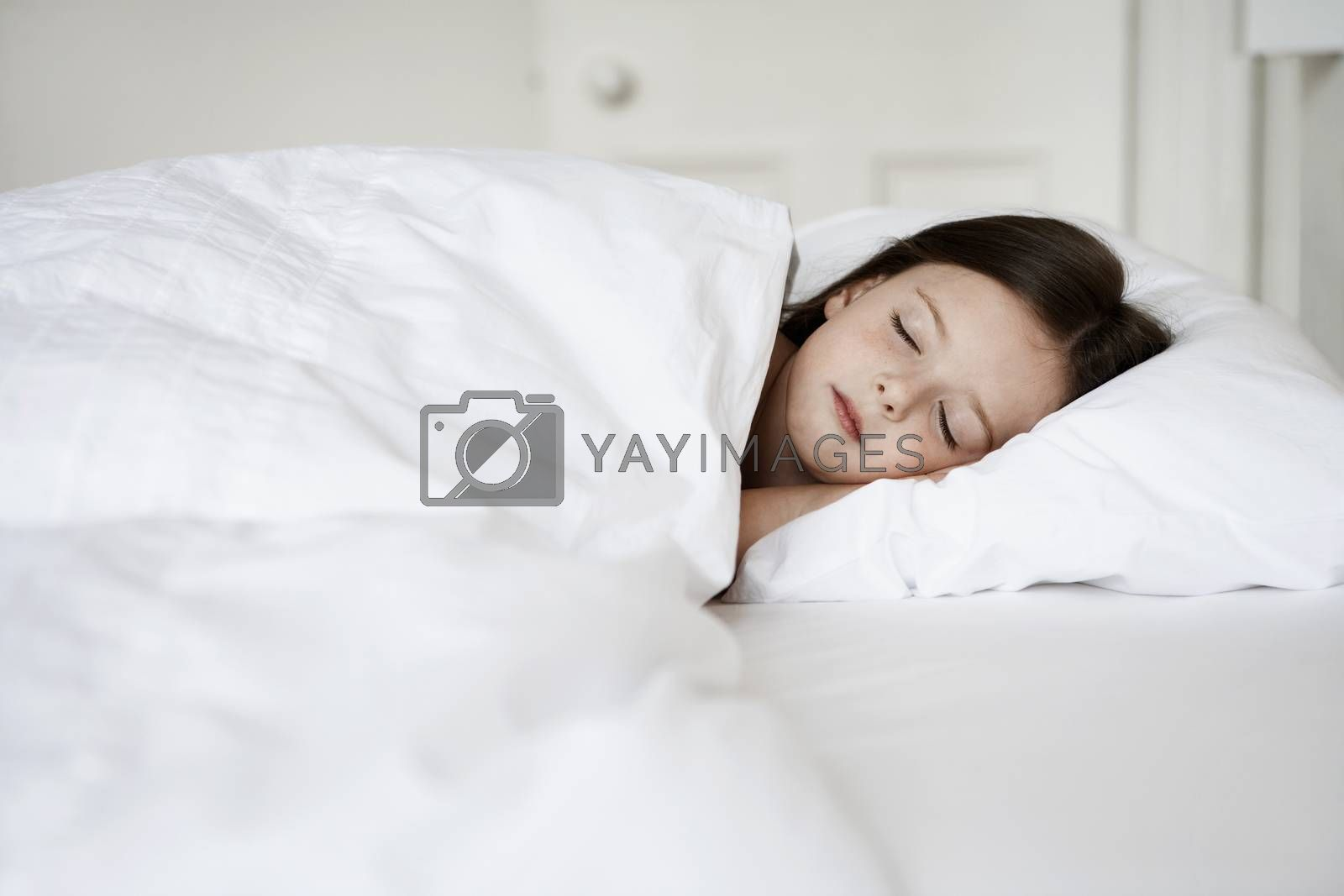 Royalty free image of Little Girl Sleeping in bed by moodboard