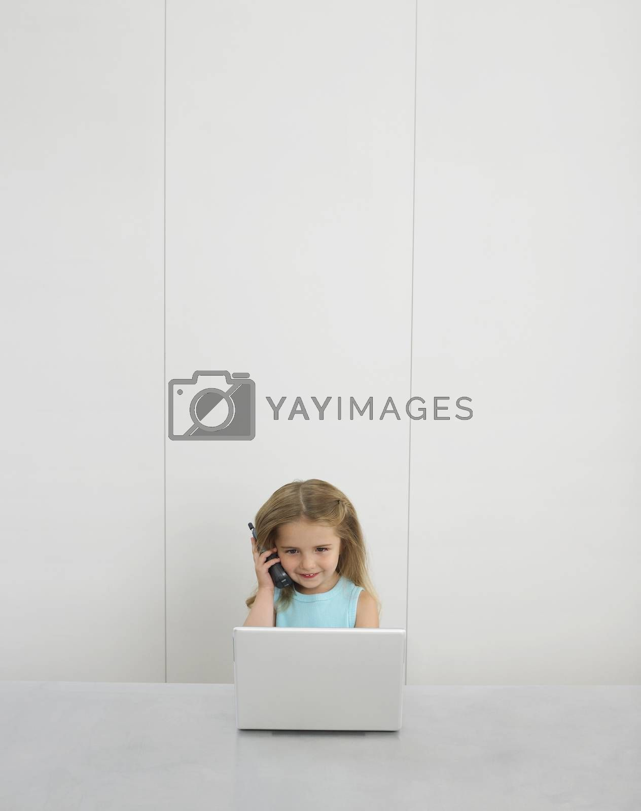 Royalty free image of Small girl by desk using cell phone and laptop by moodboard