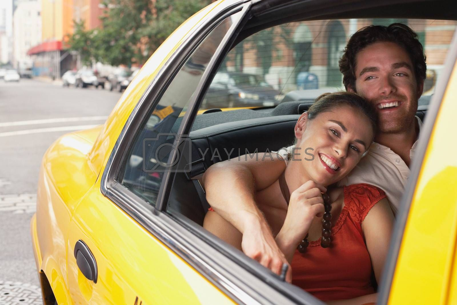 Young couple in yellow taxi on urban street by moodboard