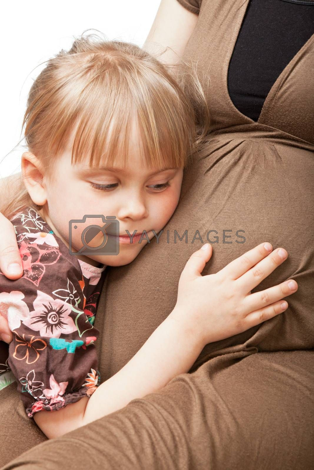 Little girl embracing pregnant mother
