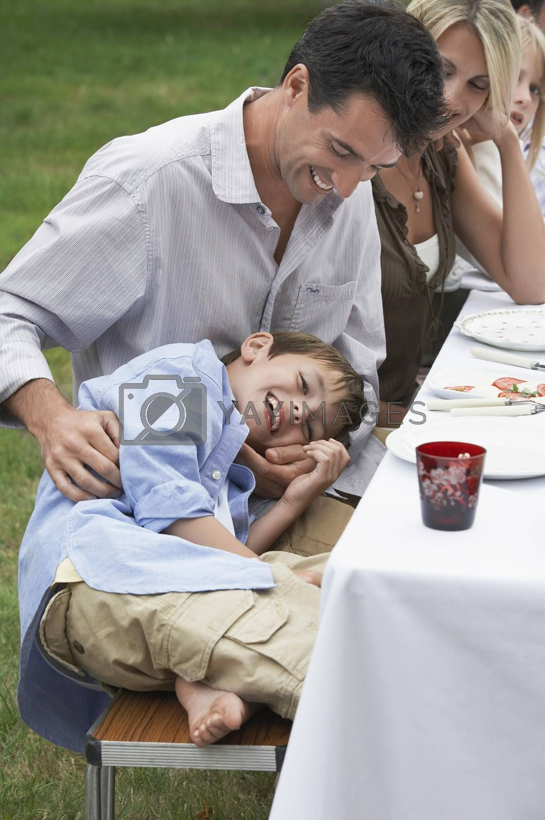Father And Son Having Fun At Dining Table
