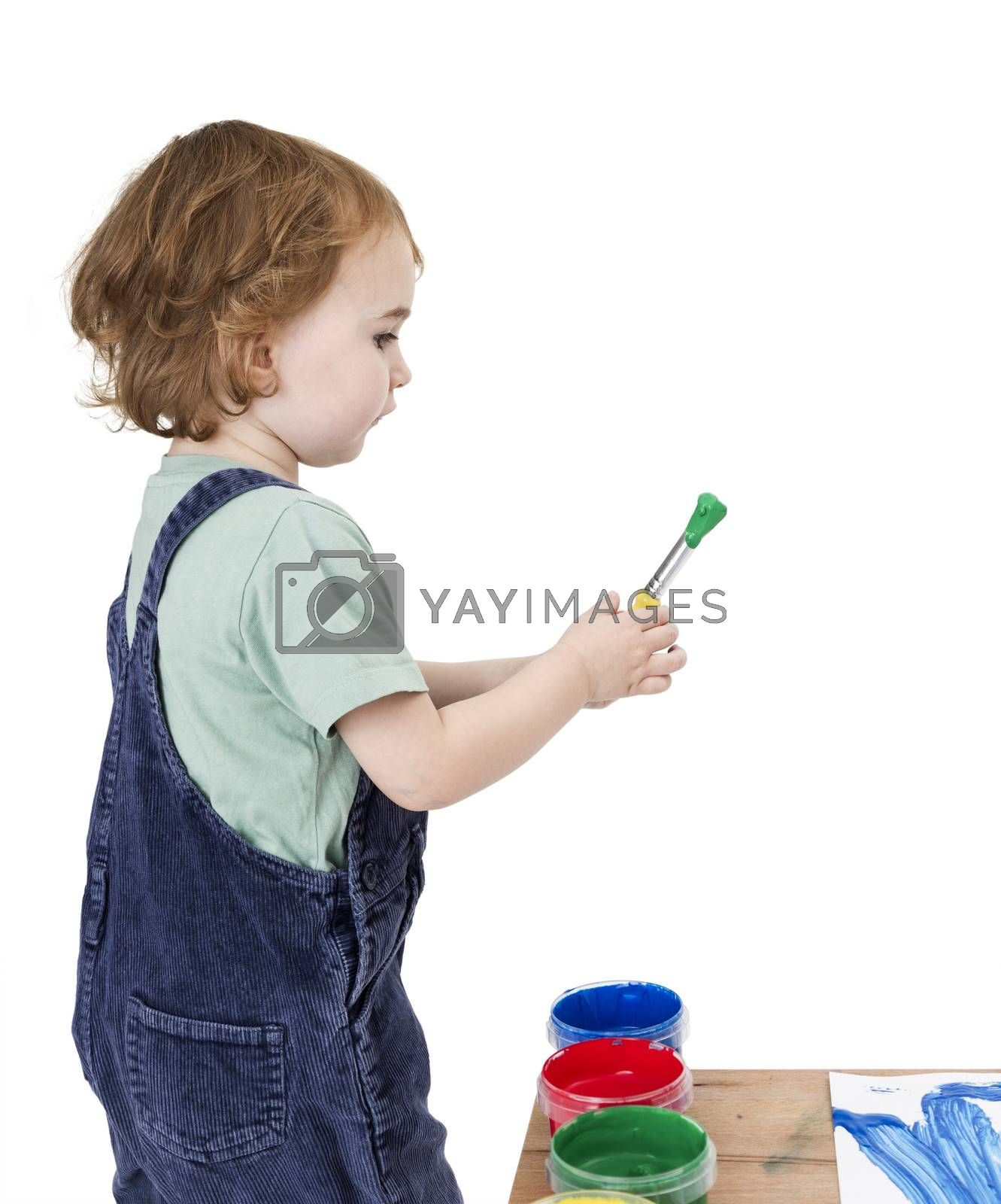 child with brush and green paint isolated on white background. Studio shot