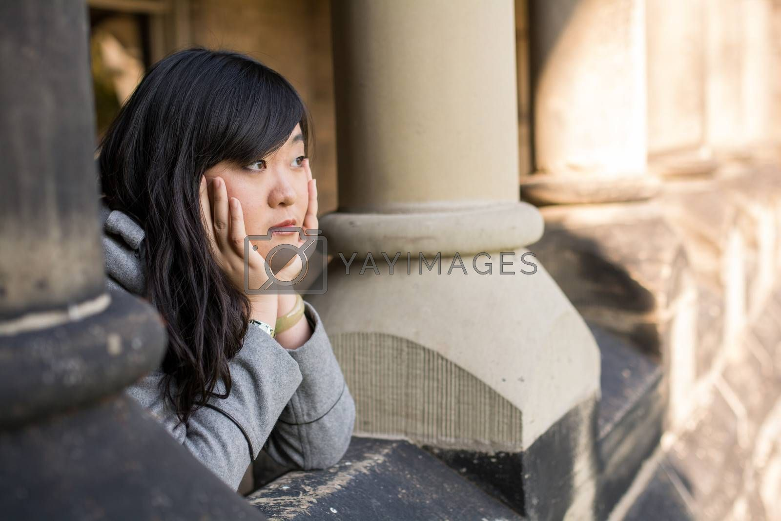 young woman leaning forward next to stone pillars