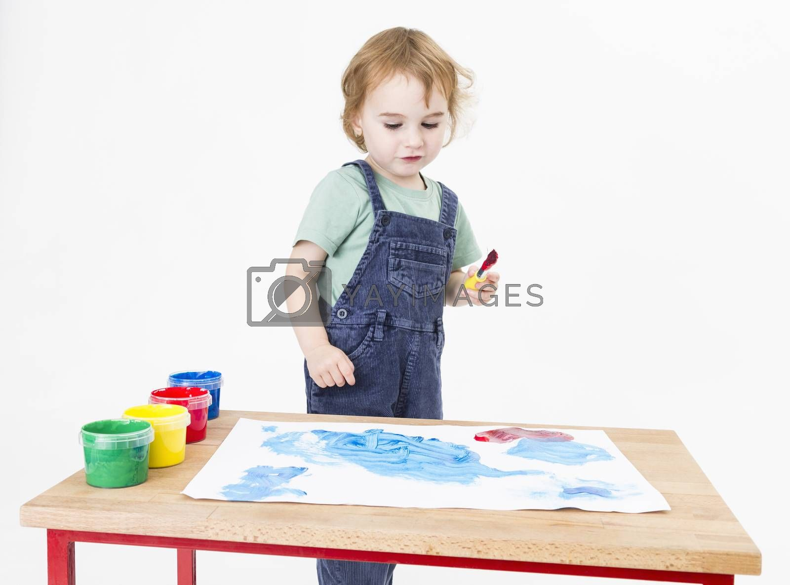 child behind small desk with blue painting. studio shot in grey background