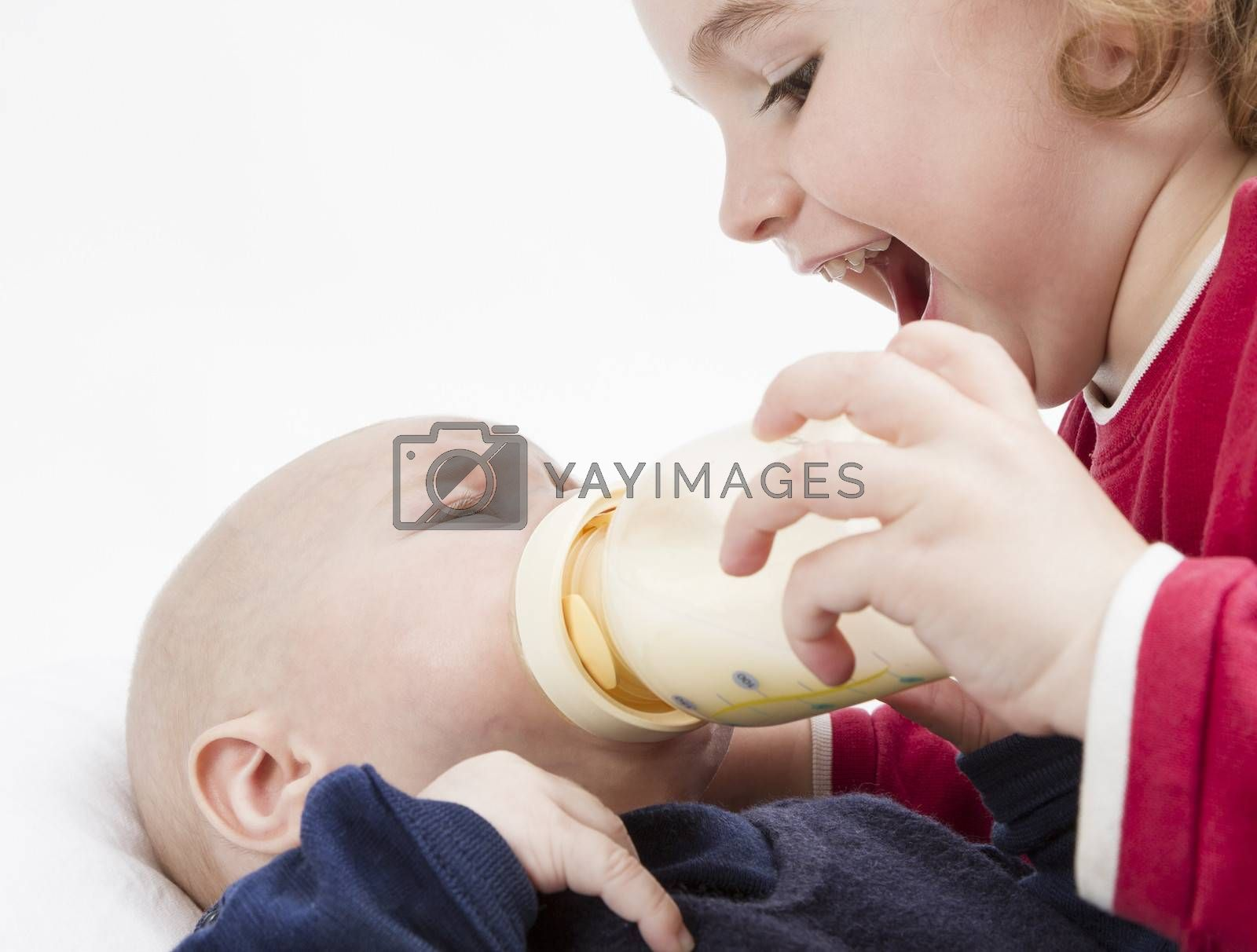 Royalty free image of young child feeding toddler with milk bottle by gewoldi
