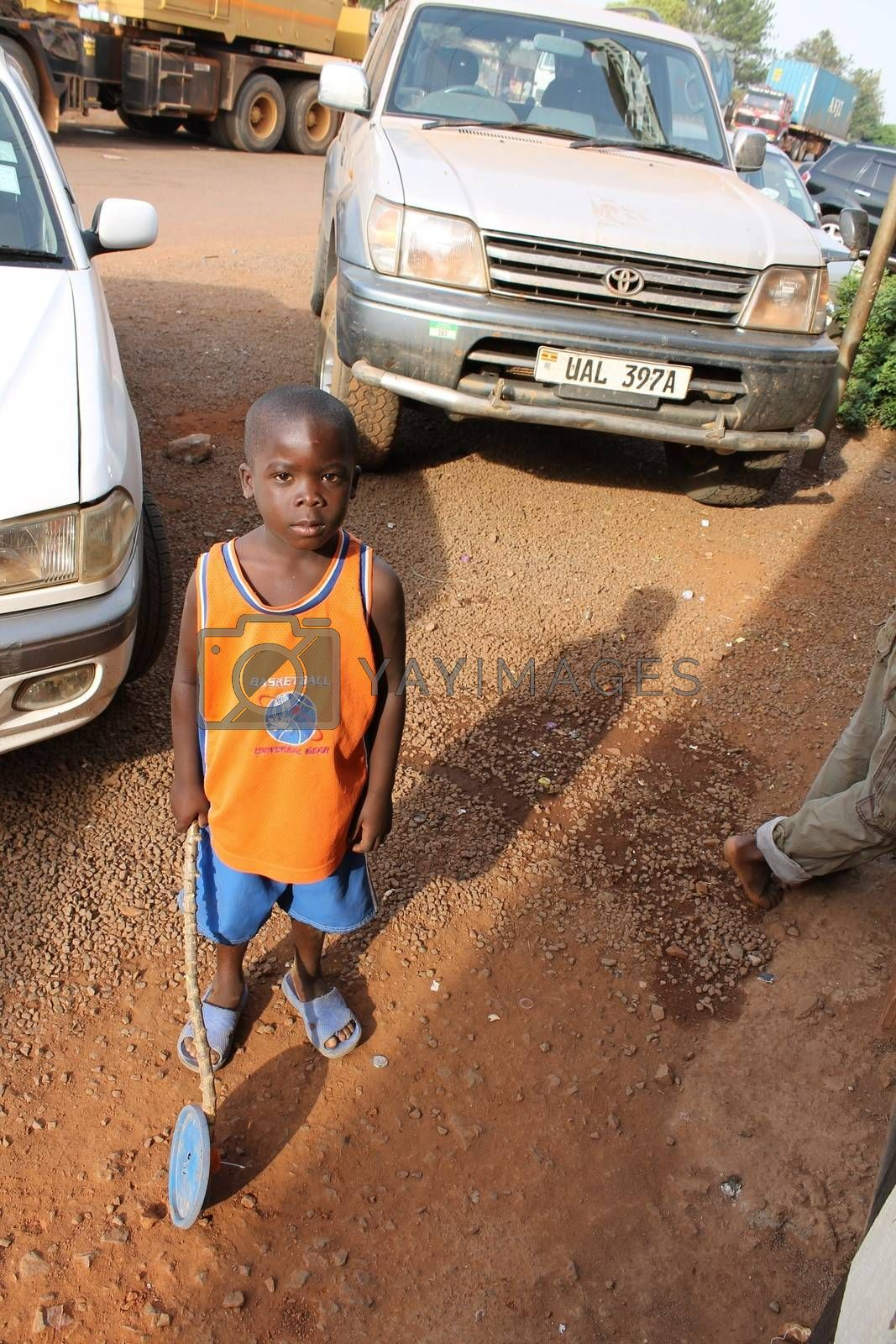 Uganda - 4 March: the Ugandan boy stands on the background of the car and looks at the photographer 4 March 2012 in Uganda.
