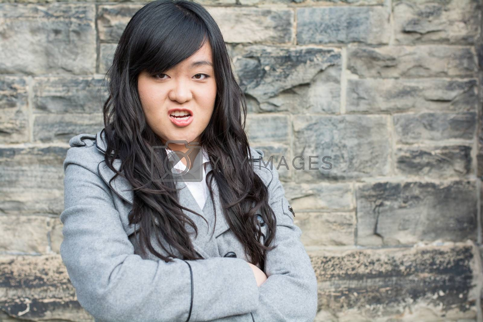 Portrait of young woman in front of a stone wall looking angry with arms crossed
