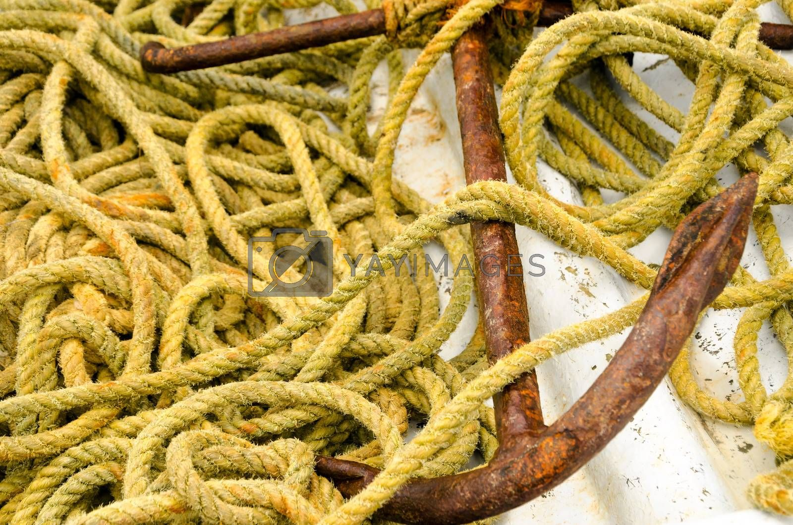 Old rusted anchor and old yellow rope