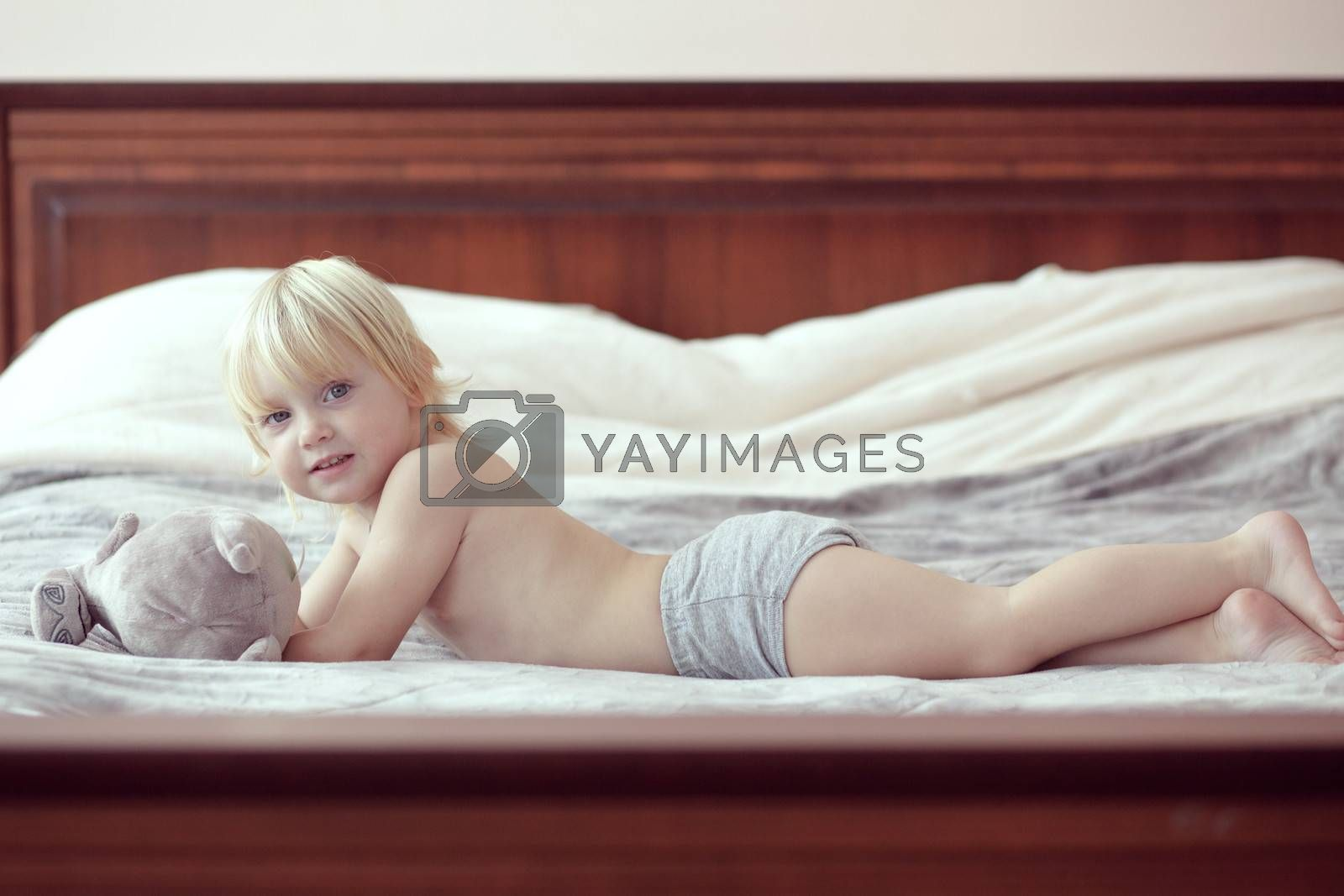 Portrait of a 2 years old child playing on his parent's bed