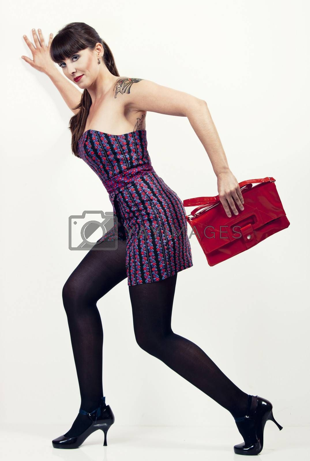 Portrait of a beautiful woman with a vintage look posing with a handbag