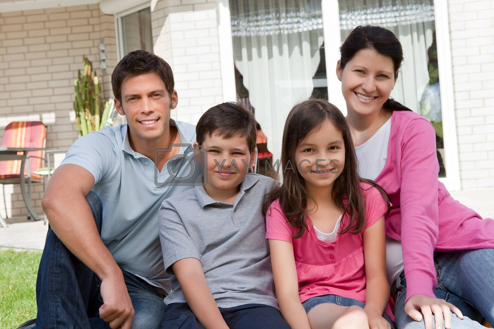 Portrait of beautiful young famliy of four sitting together outside their home