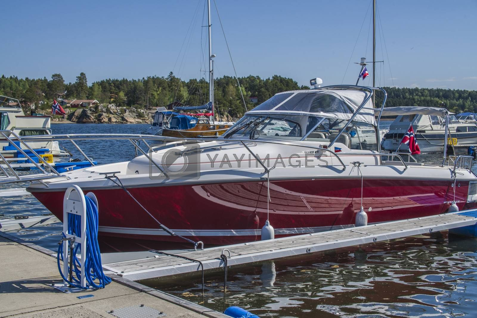 The boat is moored to the dock at the Osco marina in Halden, Norway.