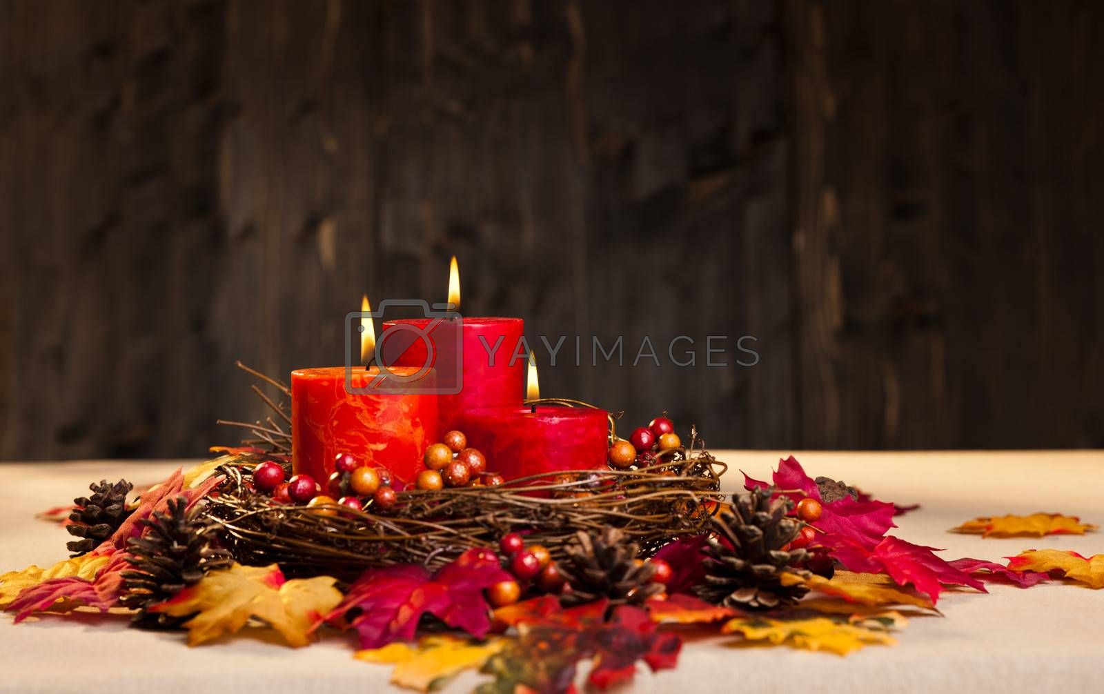 Candles in nice and beautiful colorful autumn leaves