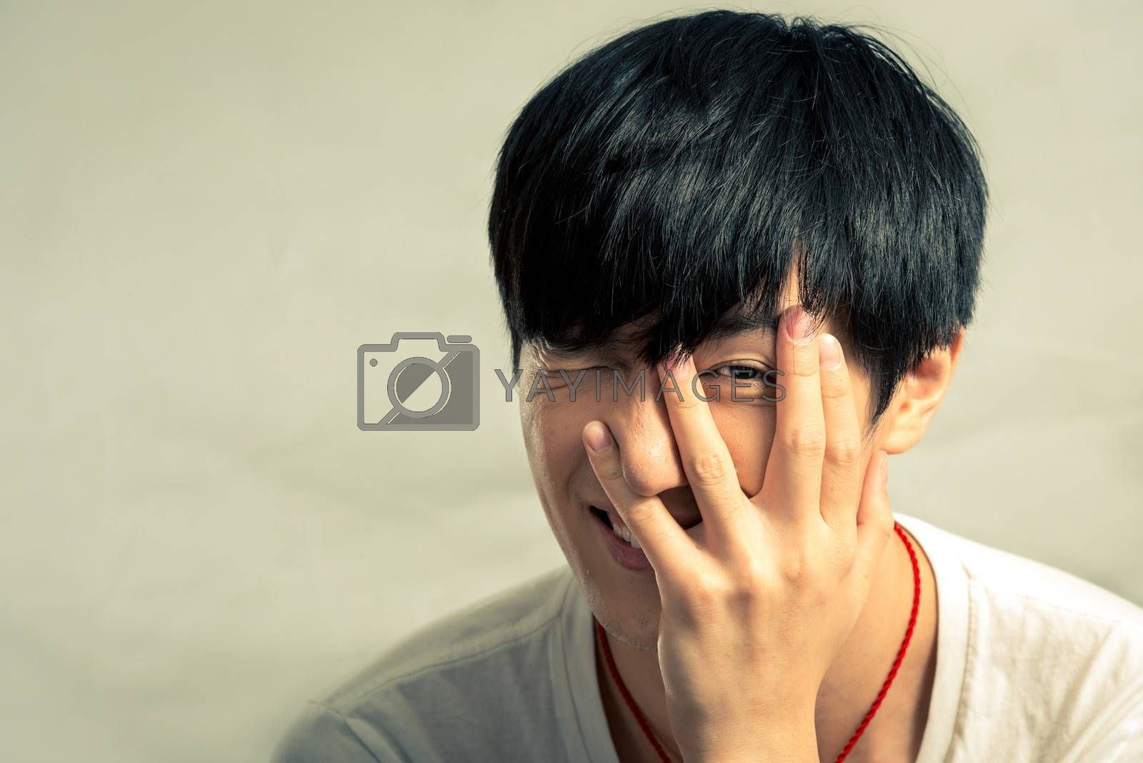 Portrait of young man smiles and looking shy, with fashion tone and background