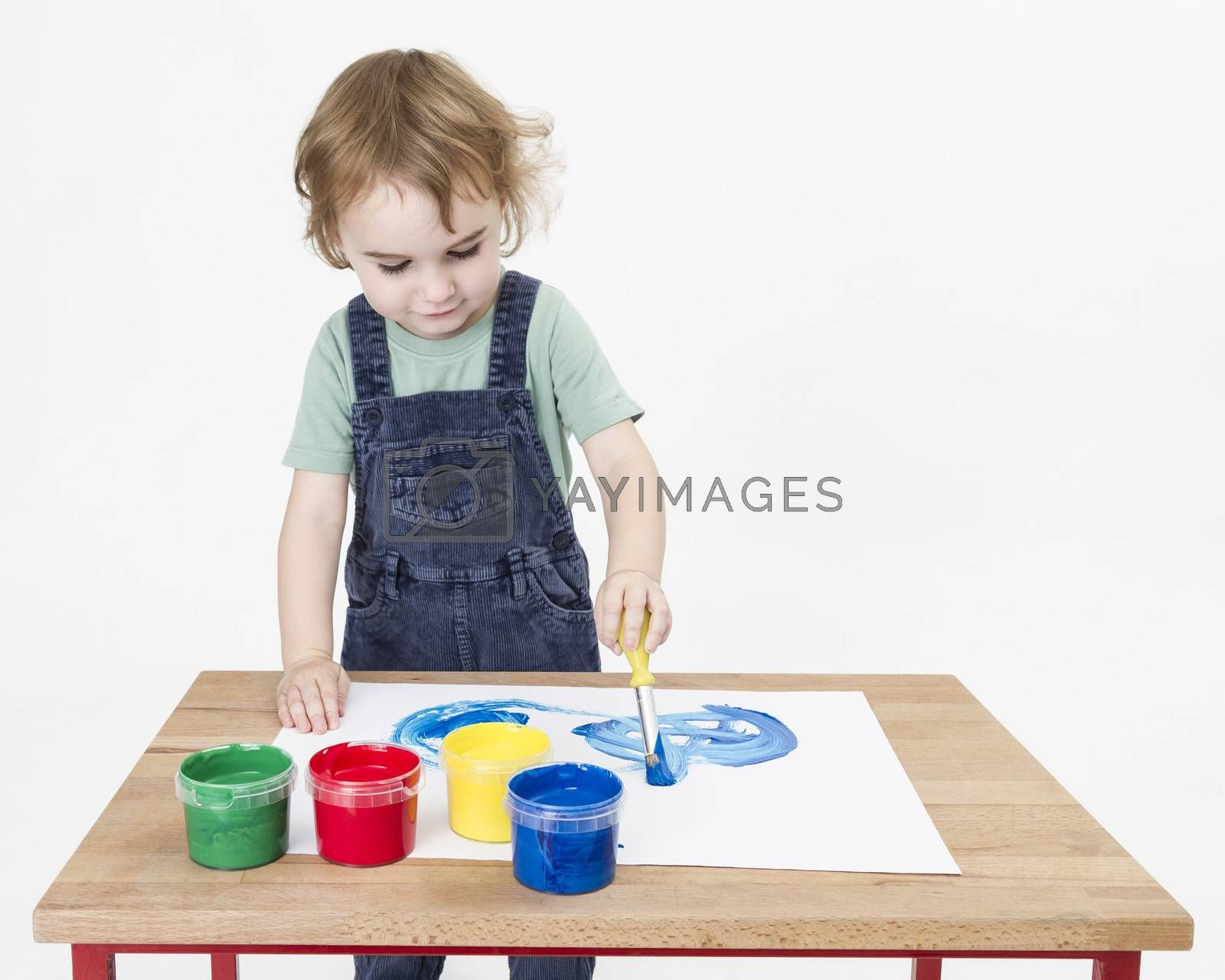 Royalty free image of cute girl painting on small desk by gewoldi