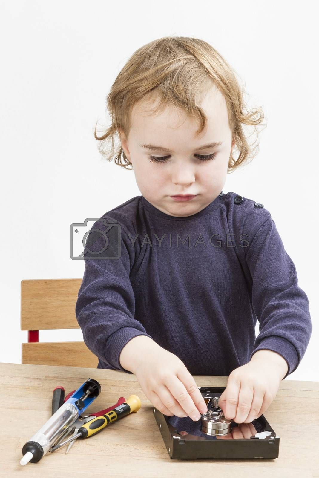 Royalty free image of little girl repairing computer parts by gewoldi