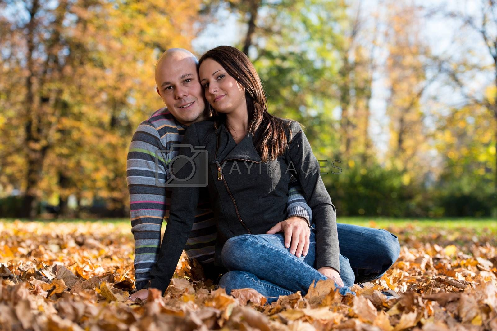 Couple Sitting Together In The Woods During Autumn