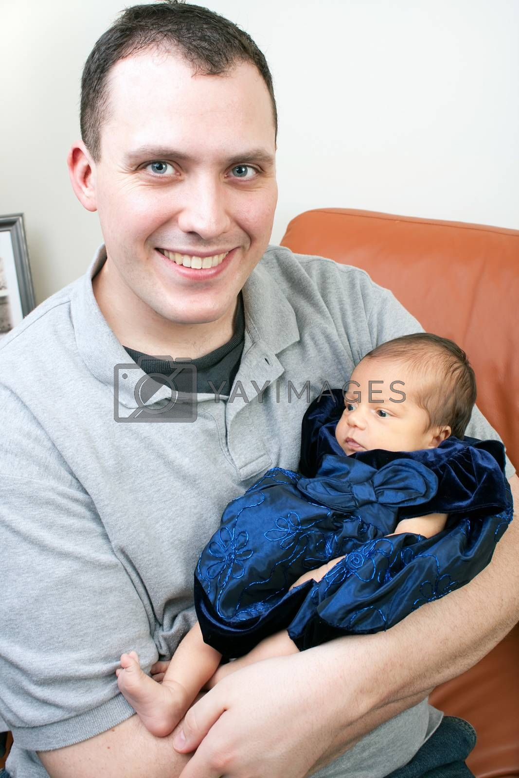 Cute newborn baby girl being held by her dad.