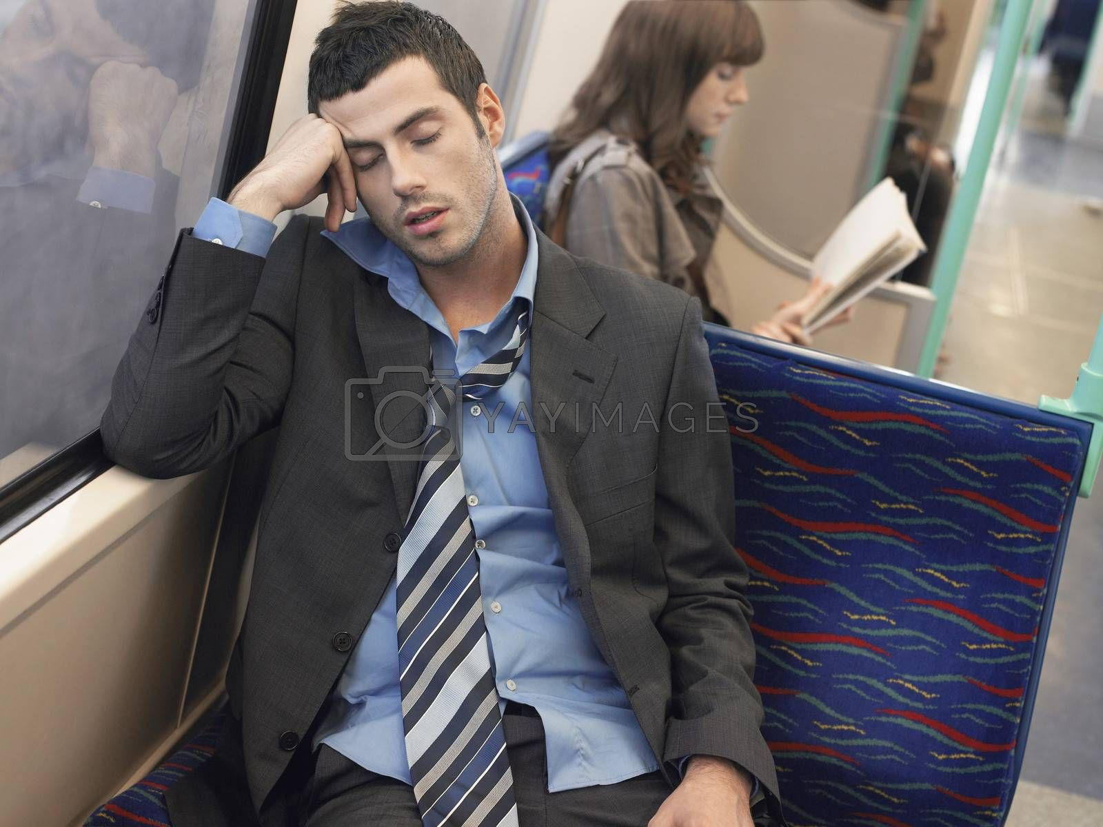 Businessman with loosened tie sleeping in commuter train by moodboard