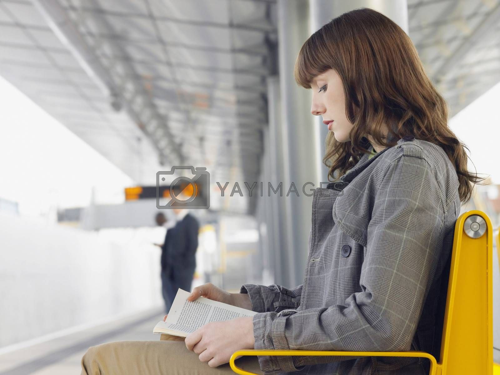 Businesswoman Reading Book At Train Station