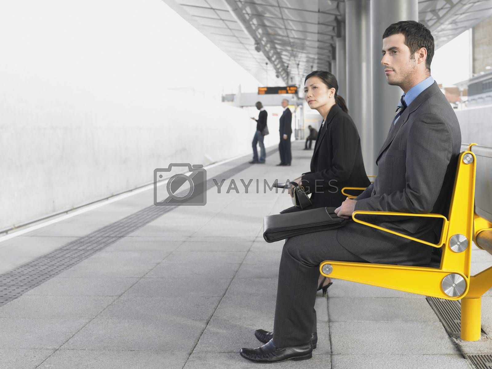 Businesspeople Sitting On Train Station Bench