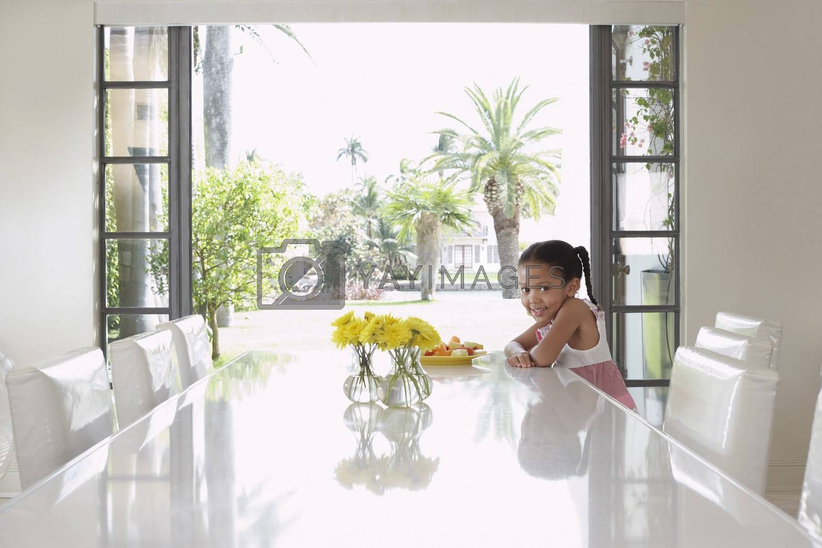 Royalty free image of Girl (5-6 years) sitting at dining table by moodboard