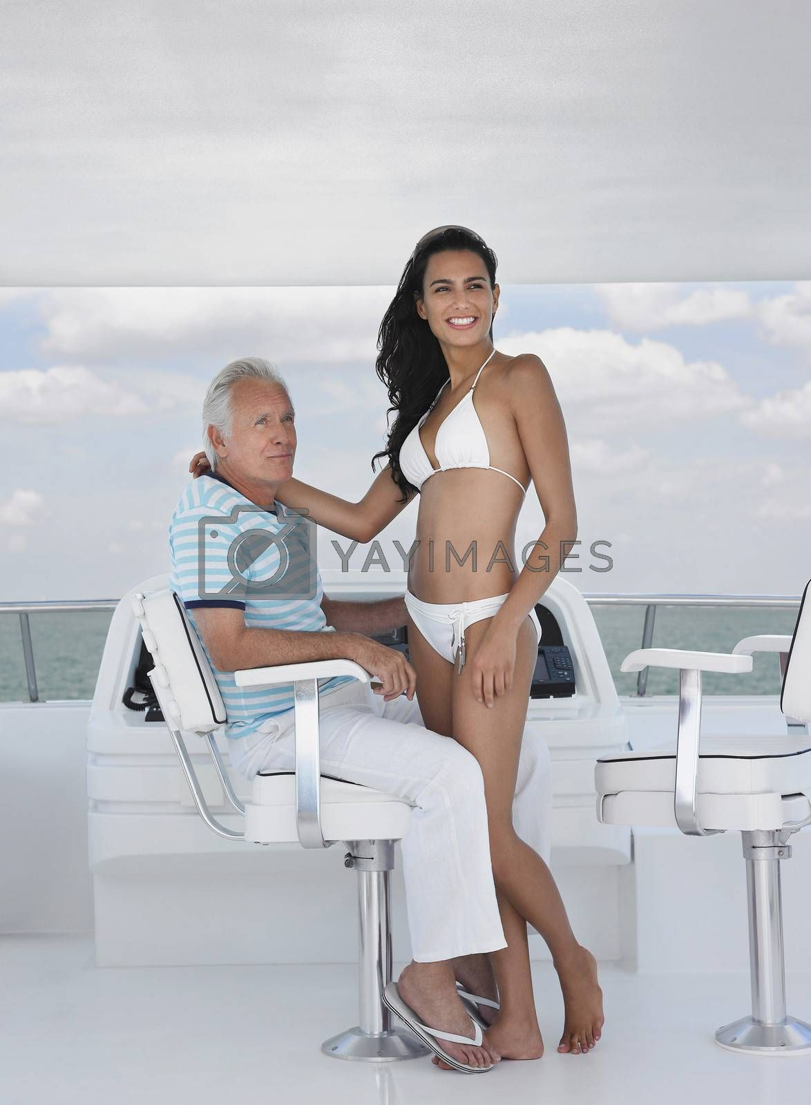 Woman Romancing With Man At Helm Of Yacht