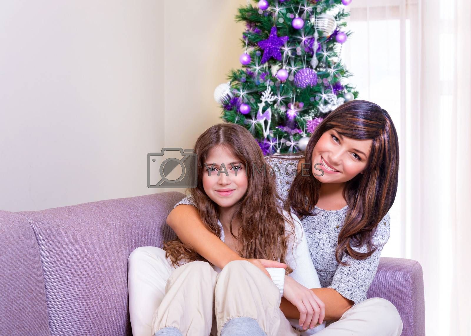 Cheerful mother and daughter sitting on the couch near beautiful decorated Christmas tree, spending New Year eve at home together, happy family concept