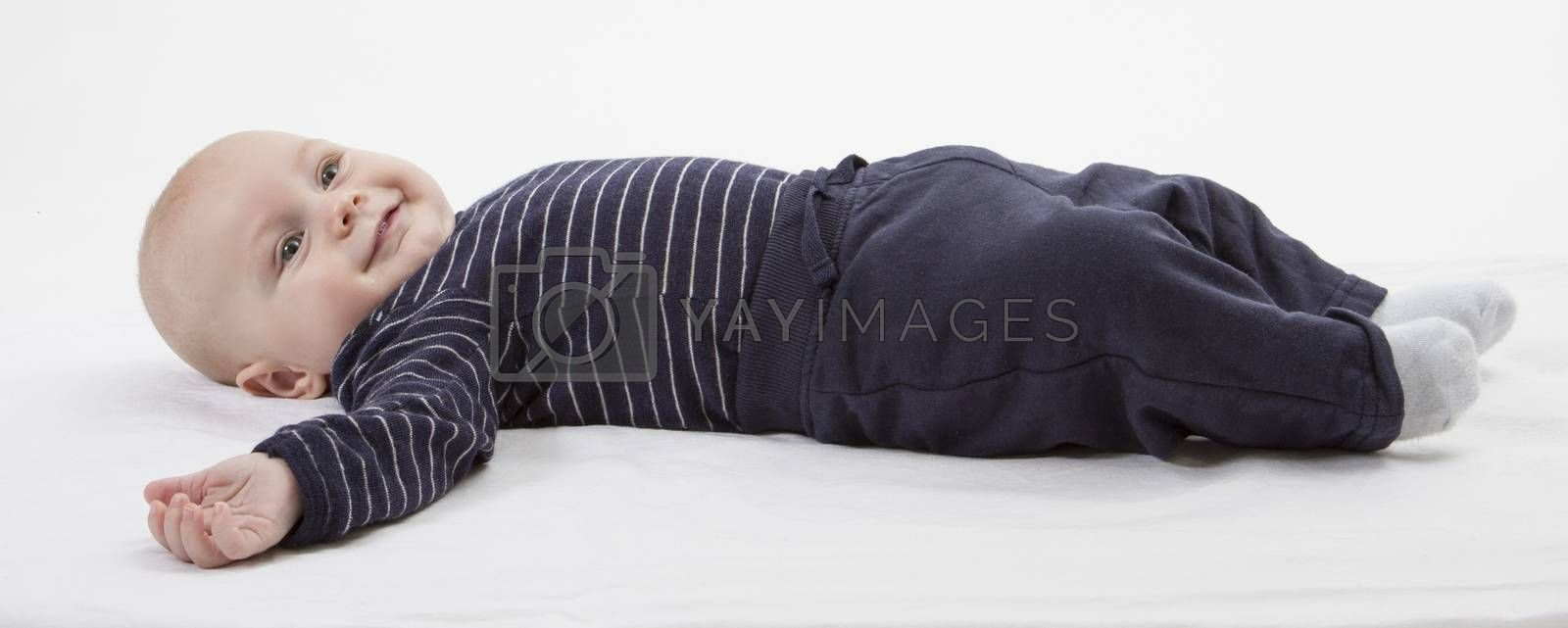 smiling toddler in blue clothing laying down. vertical image