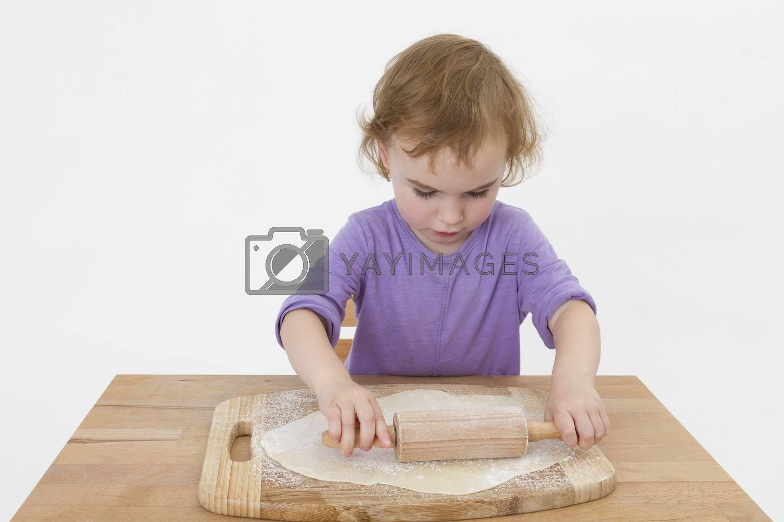 cute curly child rolling out dough. studio shot in grey background