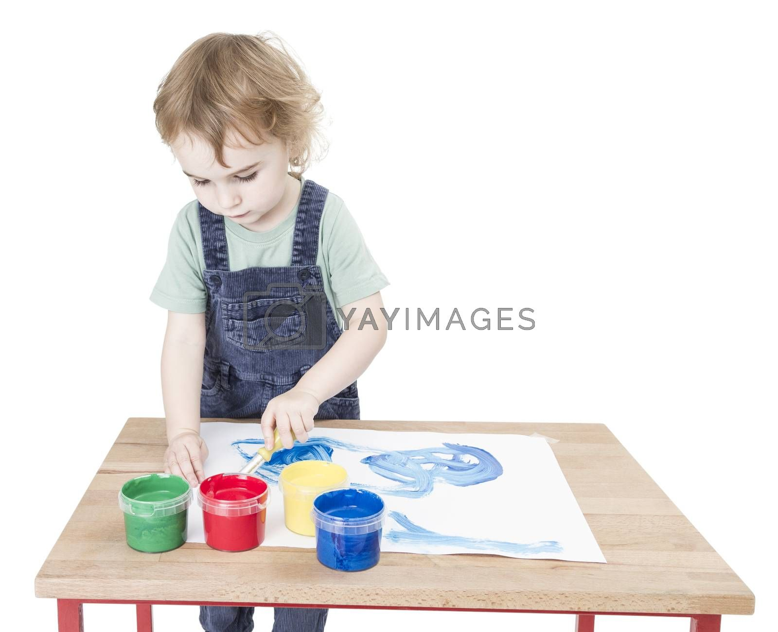 Royalty free image of child making painting on small desk by gewoldi