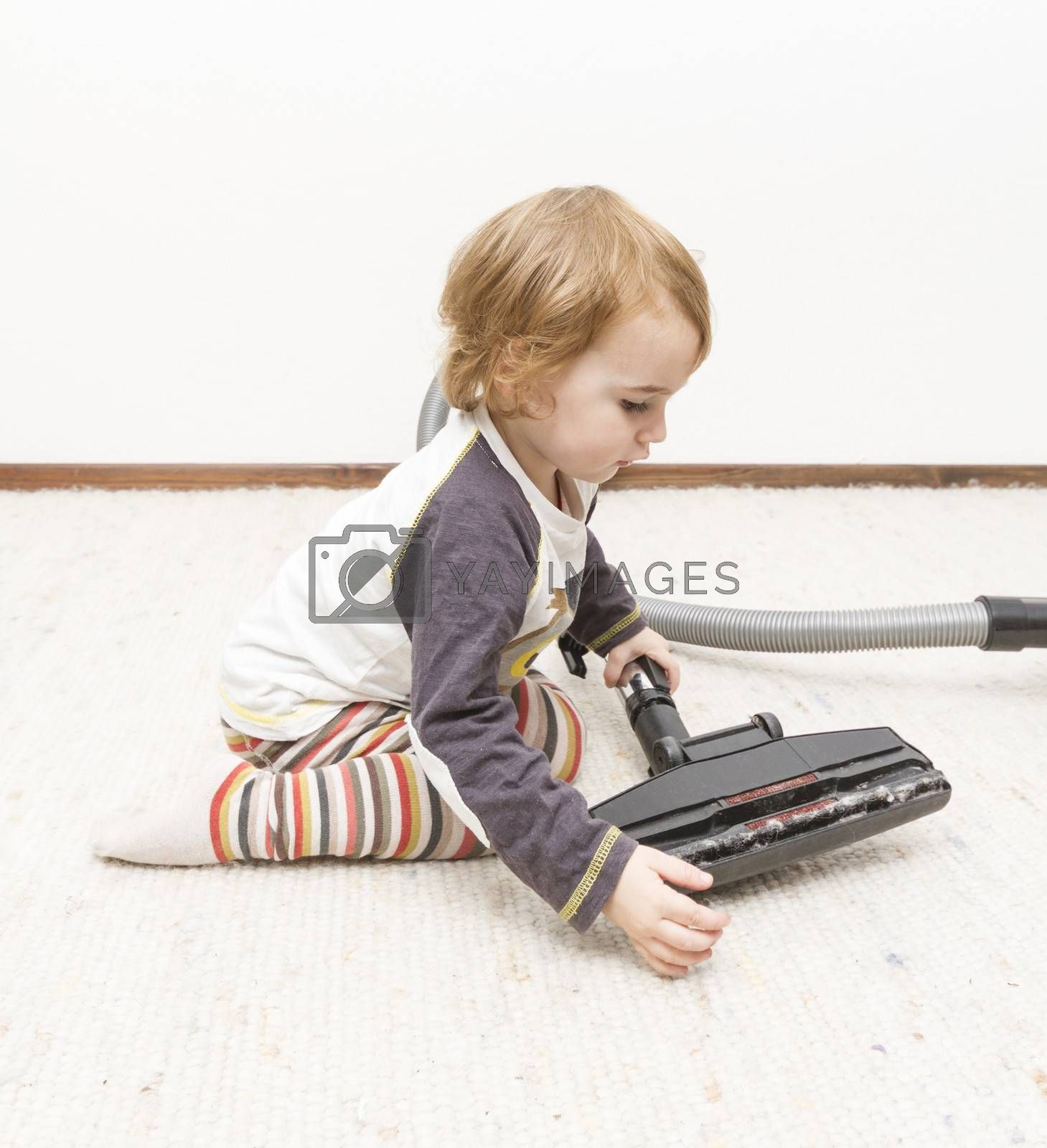 Royalty free image of young child cleaning vacuum cleaner by gewoldi