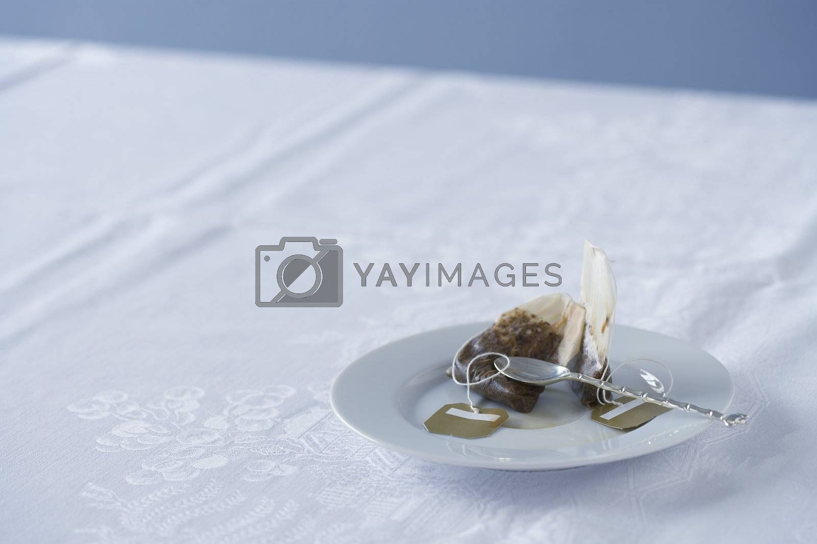 Used tea bag on saucer on table by moodboard