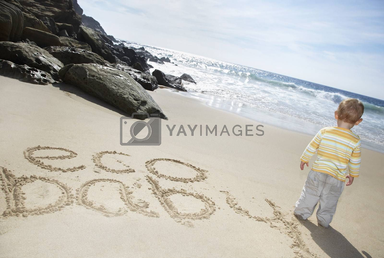 Royalty free image of Boy (1-2) standing by Eco Baby text written on beach by moodboard