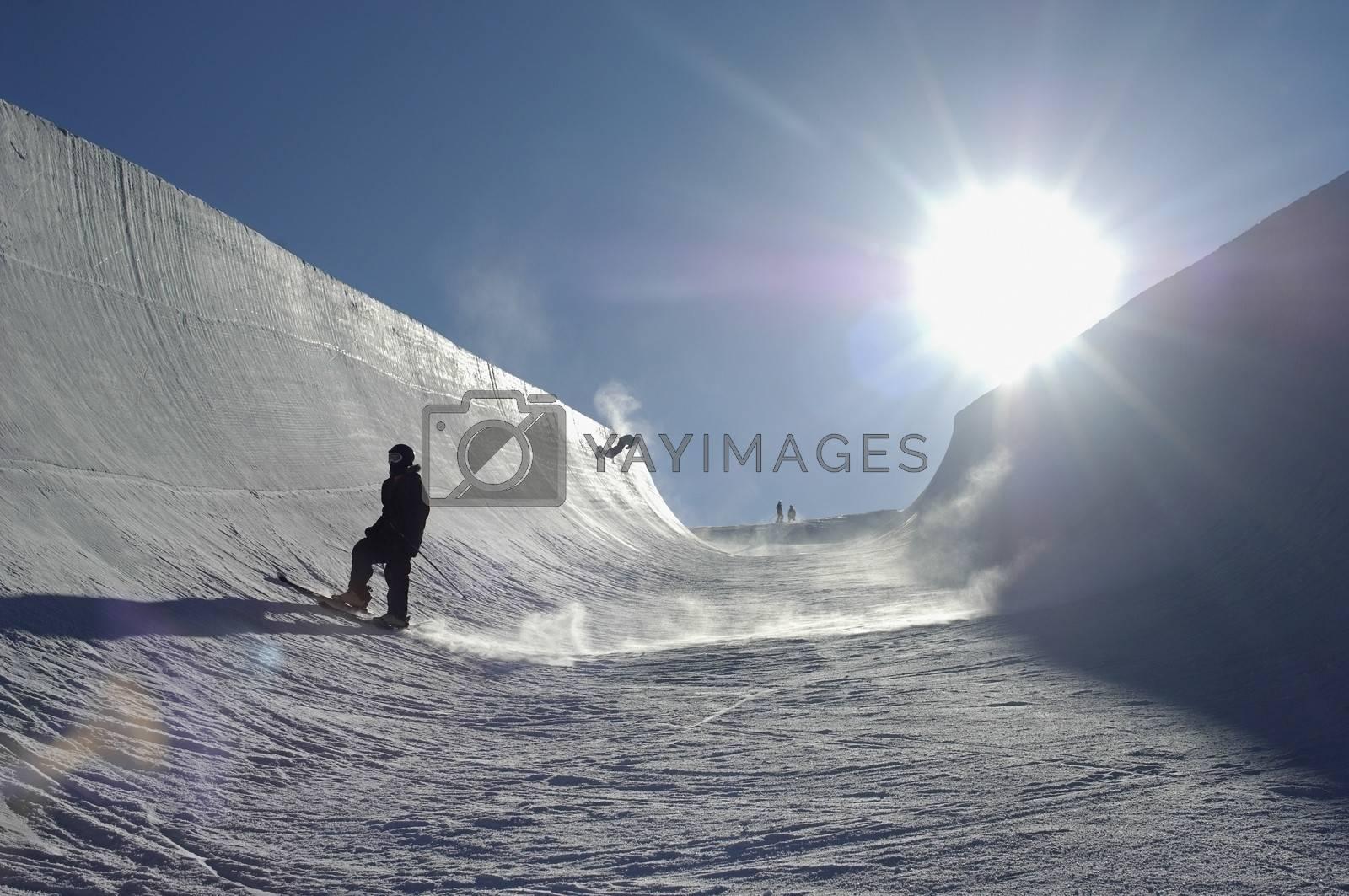 Sun Shining On People Snowboarding In Park