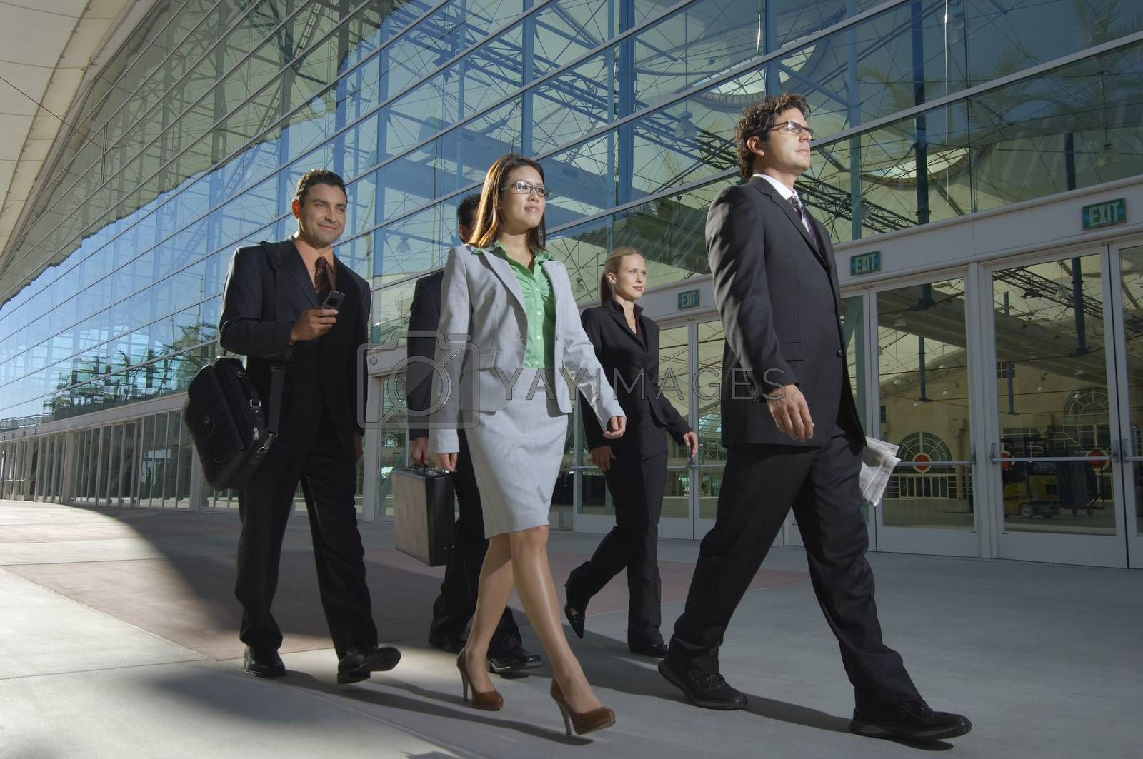 Group of business people walking past office building