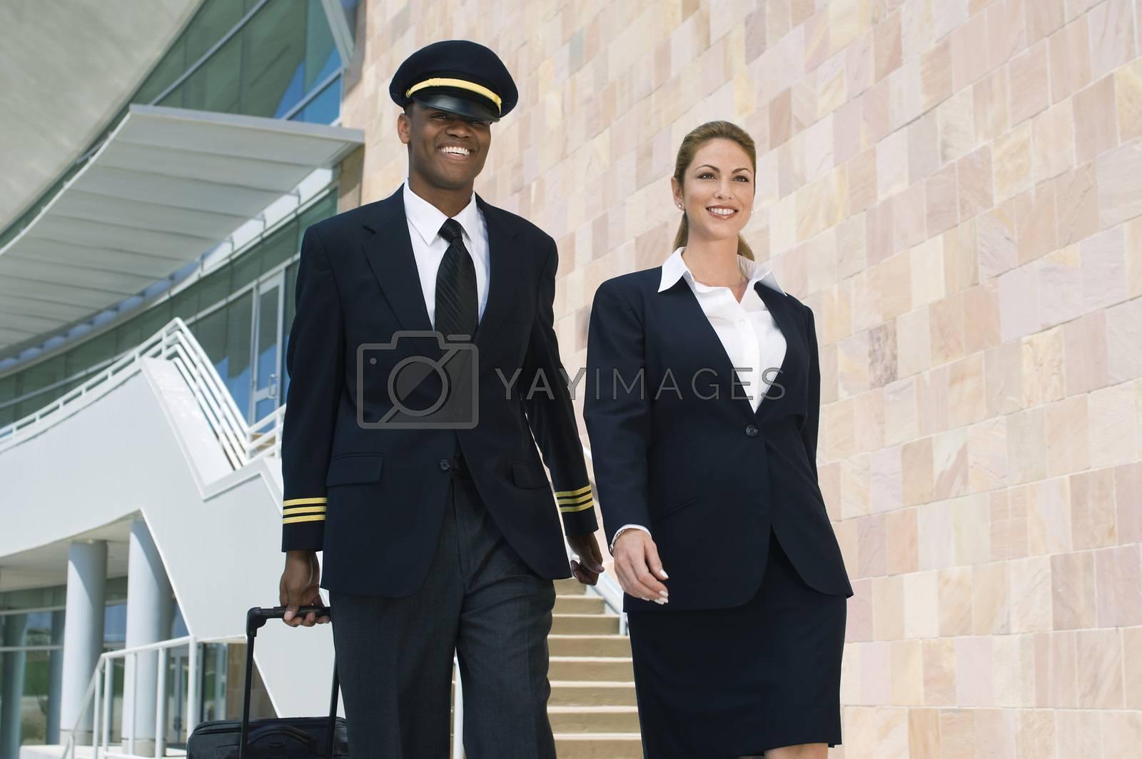 Pilot And Flight Attendant Walking Outside Building
