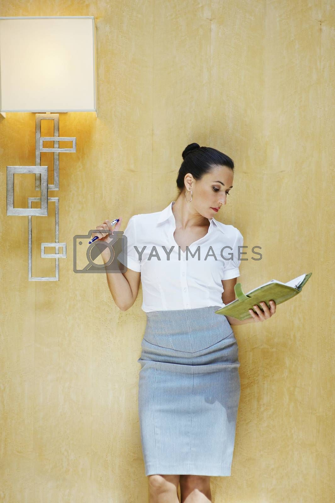 Business woman reading document in office by moodboard