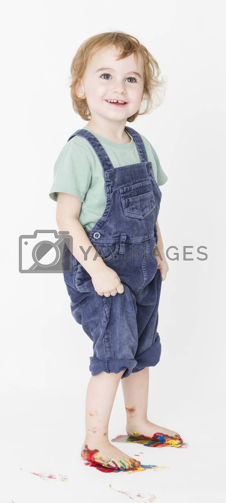 Royalty free image of child with painted feet holding trousers by gewoldi