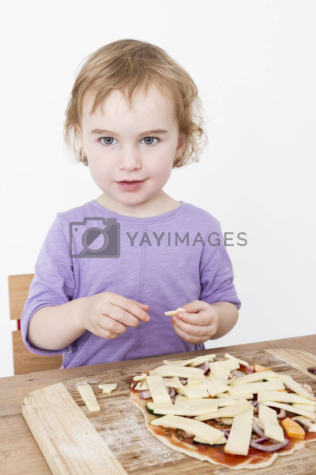 Royalty free image of cute girl making fresh pizza by gewoldi