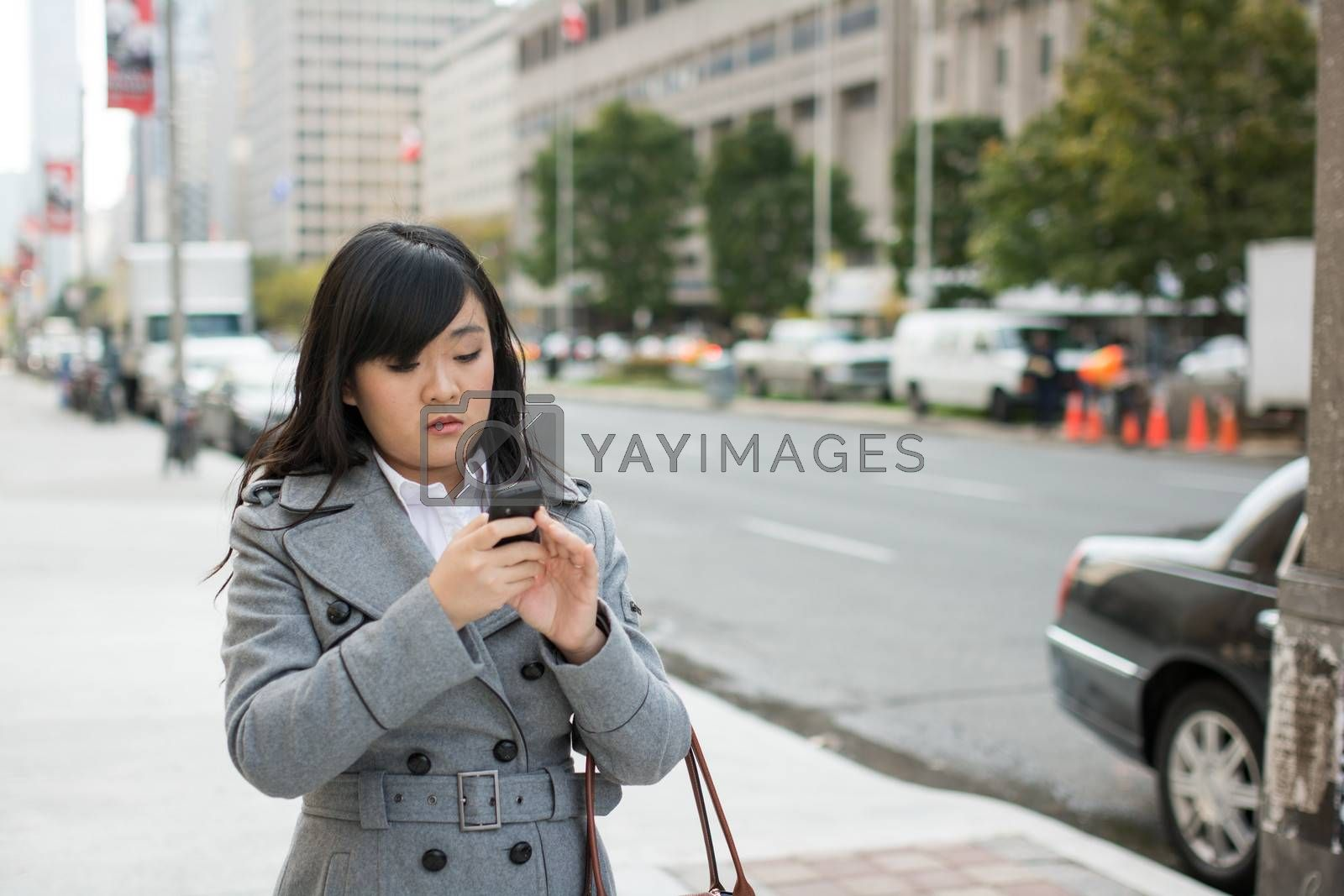 Young Asian woman texting and walking on a street in a large city