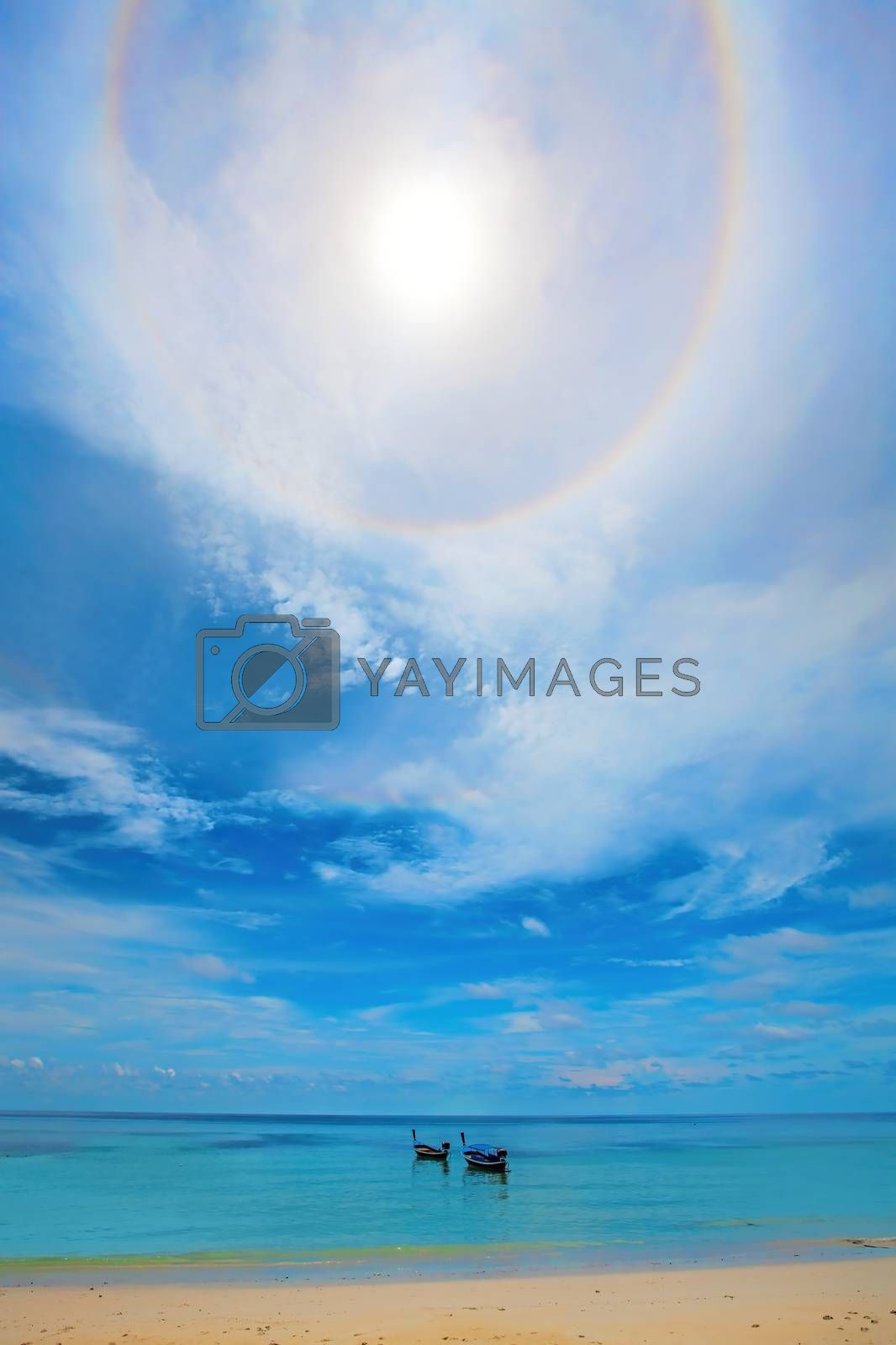 Halo around the sun over boats in the water on Koh Lipe
