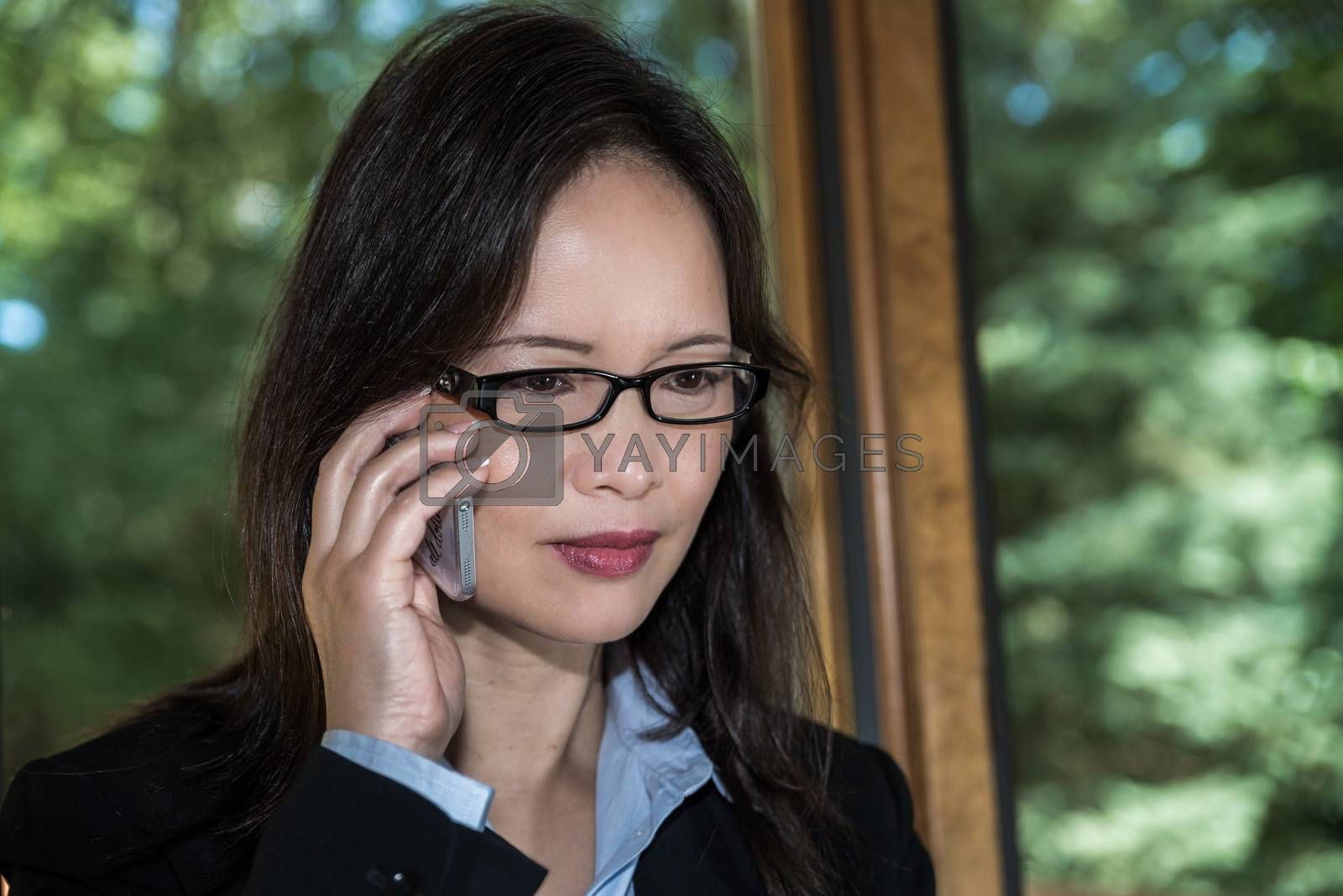 Woman in business suit speaking on a cellphone in front of a window