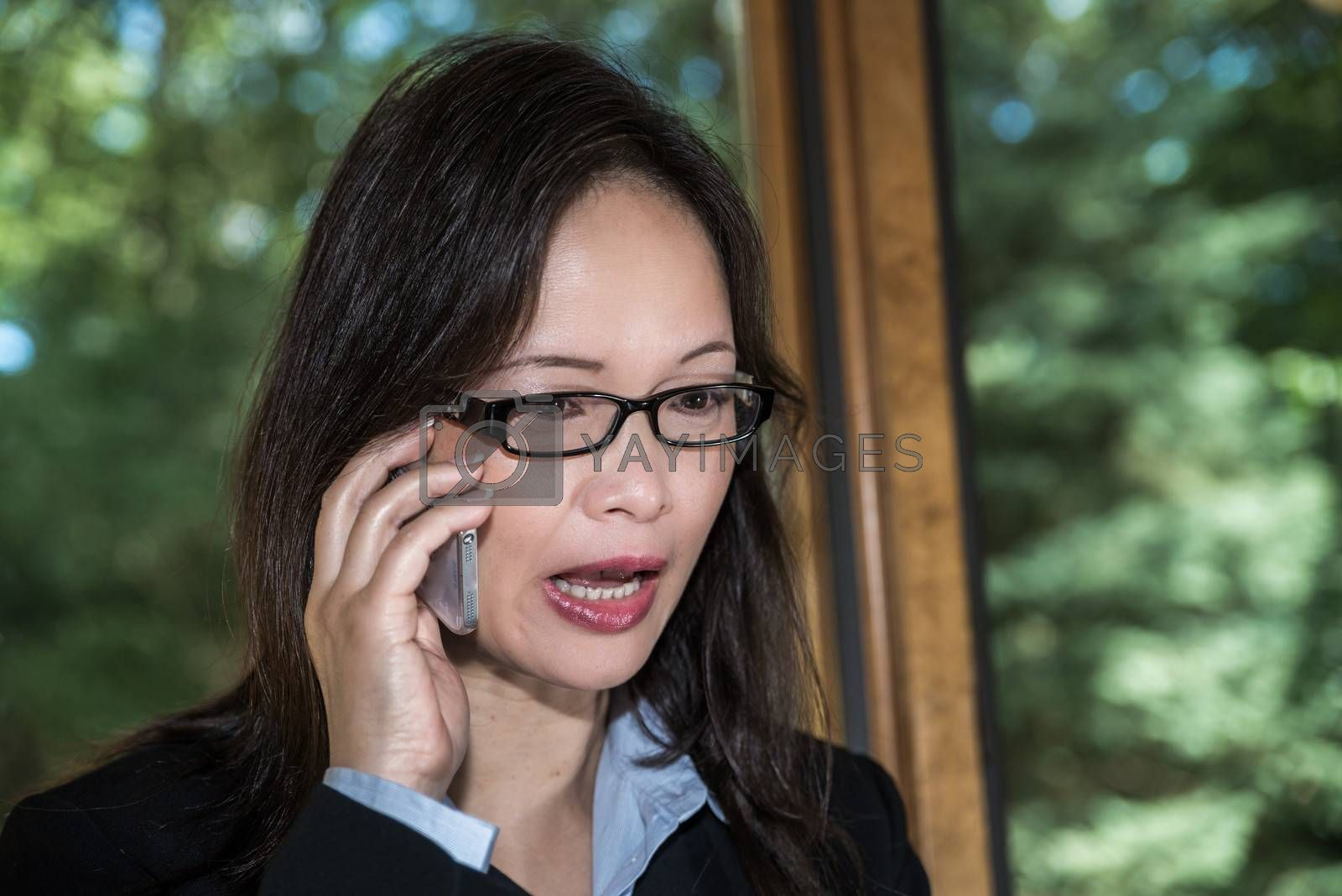 Woman in business suit speaking on a cellphone in front of a window looking upset